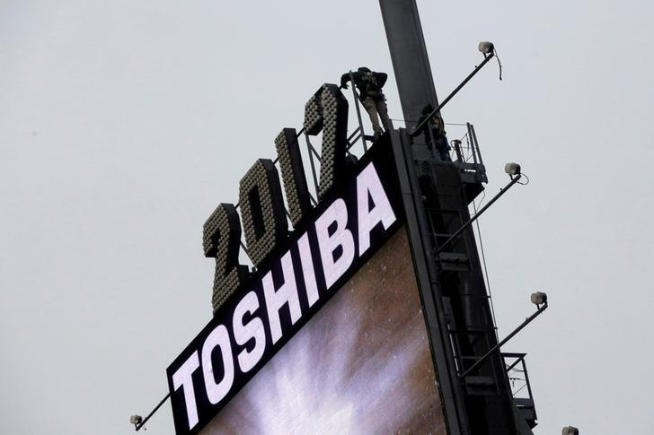 Workers prepare the New Year's eve numerals above a Toshiba sign in Times Square Manhattan, New York City, U.S., December 26, 2016. REUTERS/Andrew Kelly