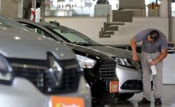 Un hombre limpia un auto en una automotora en Sao Paulo, Brasil. 5 de enero 2017. El sector automotriz de Brasil revisó a la baja el jueves su expectativa de ventas para 2017, a apenas 4 por ciento desde una cifra más cercana a los dos dígitos, citando la incertidumbre política y la recesión como los factores de mayor peso en un mercado que registró un desplome del 20 por ciento en 2016. REUTERS/Paulo Whitaker