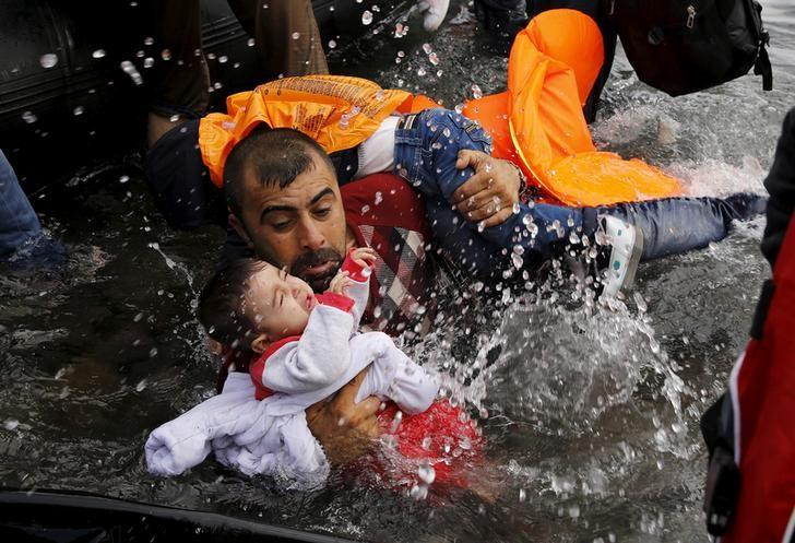 A Syrian refugee holds onto his children as he struggles to walk off a dinghy on the Greek island of Lesbos, after crossing a part of the Aegean Sea from Turkey to Lesbos September 24, 2015.  REUTERS/Yannis Behrakis/Files