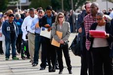Personas hacen fila para entrar a una feria de empleo en el condado de Nassau en Nueva York. 7 de octubre de 2014. El empleo en Estados Unidos aumentó menos de lo previsto en diciembre, pero un repunte en los salarios apuntaba a un impulso sostenido en el mercado laboral que deja a la economía encaminada a un crecimiento más sólido y a más alzas de tasas de interés por parte de la Reserva Federal este año. REUTERS/Shannon Stapleton/