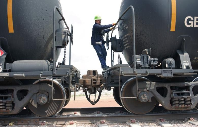 A worker climbs off a crude oil train after setting the handbrake at the Eighty-Eight Oil LLC's transloading facility in Ft. Laramie, Wyoming July 15, 2014. REUTERS/Rick Wilking