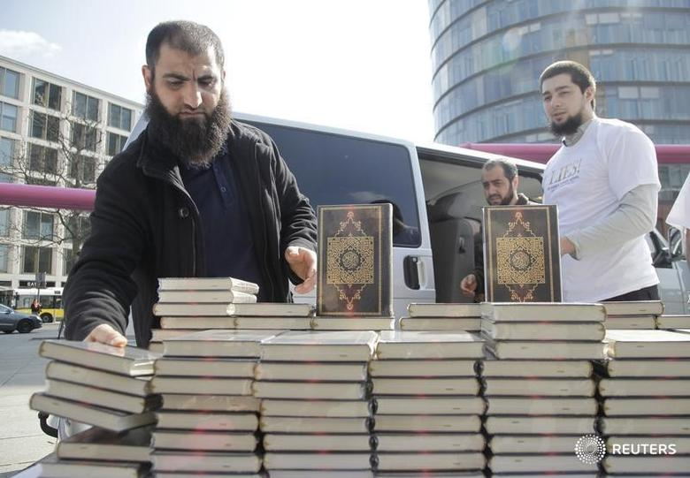 Supporters of ultra-conservative Salafist Muslim group set up a stand handing out German-language versions of the Koran at the Potsdamer Platz square in downtown Berlin, April 14, 2012. REUTERS/Tobias Schwarz