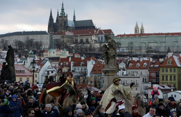 Men dressed as the Three Kings greet spectators as they ride camels during the Three Kings procession across the medieval Charles bridge, as a part of a re-enactment of the Nativity scene, in Prague, Czech Republic January 6, 2017. REUTERS/David W Cerny