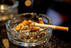 Сигарета и окурки в пепельнице в баре Вены. Курение обходится мировой экономике более чем в $1 триллион в год, и к 2030 году от него будут гибнуть на треть больше людей, чем сейчас, показало исследование Всемирной организации здравоохранения (ВОЗ) и Национального института онкологии США, обнародованное во вторник.  REUTERS/Leonhard Foeger