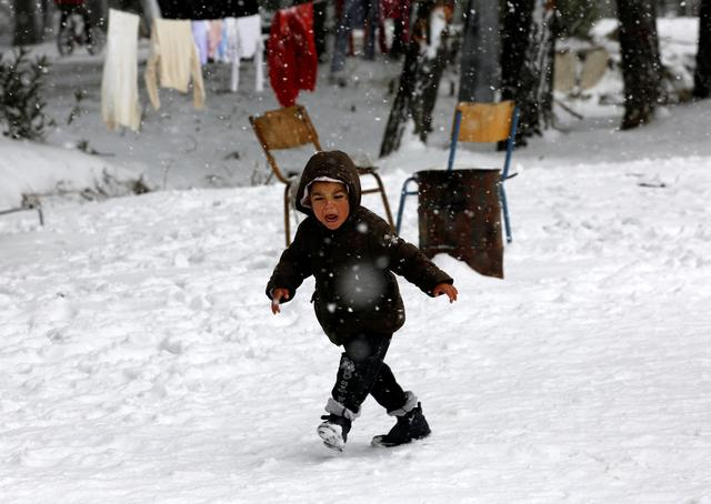A stranded Syrian refugee boy cries as he braves through a showstorm at a refugee camp north of Athens January 10, 2017.REUTERS/Yannis Behrakis
