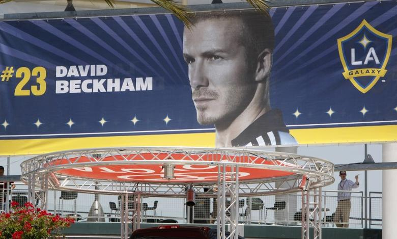 A man walks past a David Beckham advertising poster at Los Angeles Galaxy stadium shop in Carson, California, July 20, 2007. REUTERS/Toby Melville