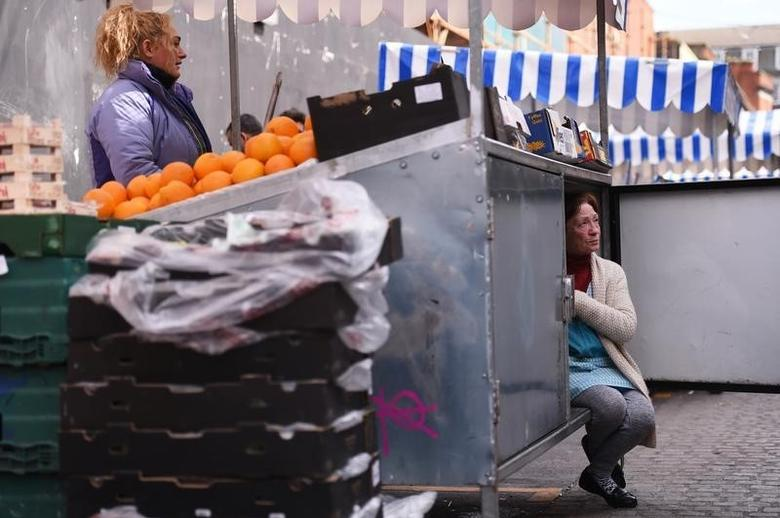 A woman arranges her stall as she chats to her friend at the Moore Street fruit and vegetable market in Dublin, Ireland April 23, 2016. REUTERS/Clodagh Kilcoyne