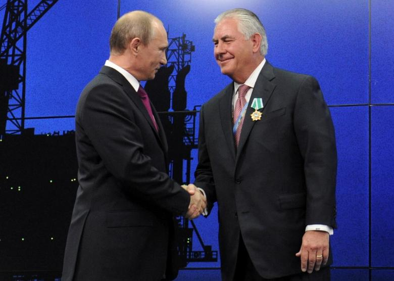 FILE PHOTO: Russian President Vladimir Putin shakes hands with Exxon Mobil Chief Executive Rex Tillerson during a ceremony awarding heads and employees of major energy companies in St. Petersburg, Russia June 21, 2013. Sputnik/Michael Klimentyev/Kremlin/via REUTERS/File Photo