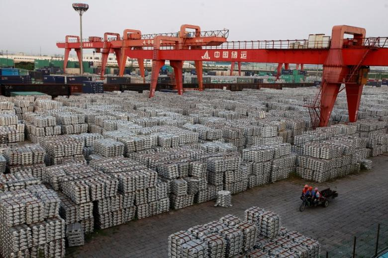 Workers ride on an motor rickshaw through an aluminium ingots depot in Wuxi, Jiangsu province in this September 26, 2012 file picture. REUTERS/Aly Song/File Photo