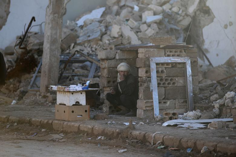 A man sells cigarettes near rubble of damaged buildings in al-Rai town, northern Aleppo countryside, Syria January 13, 2017. REUTERS/Khalil Ashawi