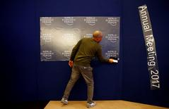 A worker prepares the logo of the World Economic Forum in the congress center of the annual meeting of the World Economic Forum (WEF) in Davos, Switzerland January 16, 2017.  REUTERS/Ruben Sprich