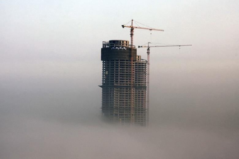 A building under construction is seen in fog in Rizhao, Shandong province, February 26, 2014.  REUTERS/Stringer