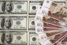 Долларовые и рублевые купюры в Сараево 9 марта 2015 года. Банк России по просьбе Минфина с февраля начнет проводить валютные интервенции на внутреннем рынке на фоне стремления властей снизить влияние нефтяных цен на экономику и бюджет, говорится в сообщении Минфина.  REUTERS/Dado Ruvic