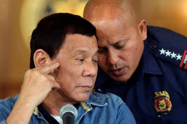 1月30日、フィリピン国家警察のデラロサ長官は、麻薬犯罪捜査を悪用するなどの不正行為を行った警官が一掃されるまで、麻薬捜査活動を中断すると明らかにした。写真左はドゥテルテ大統領。マニラで29日撮影(2017年 ロイター/Ezra Acayan)