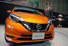 Nissan Executive Vice President Hideyuki Sakamoto poses with the hybrid version of Nissan Note, which uses the carmaker's  e-Power system, in the showroom at the carmaker's headquarters in Yokohama, Japan, January 13, 2017. Picture taken January 13, 2017.    REUTERS/Toru Hanai