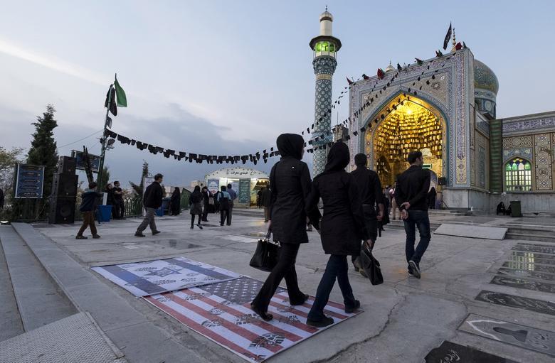 FILE PHOTO: People step on a U.S. flag (R) and an Israeli flag at a shrine on Ashura in the north of Tehran October 24, 2015. REUTERS/Raheb Homavandi/TIMA/File Photo