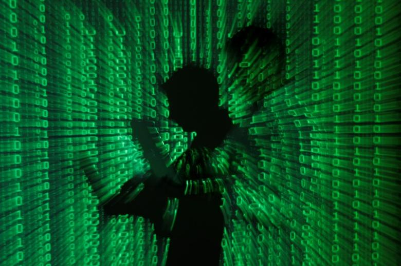 An illustration picture shows a projection of binary code on a man holding a laptop computer, in an office in Warsaw June 24, 2013. REUTERS/Kacper Pempel/Illustration/File Photo