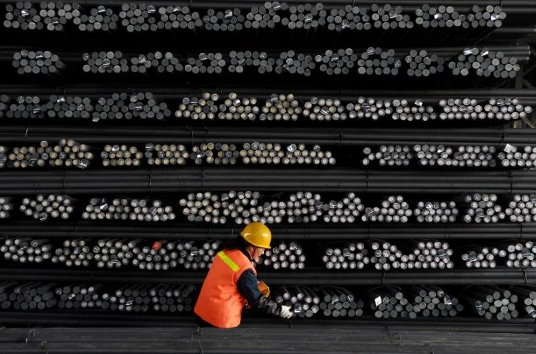 A labourer marks steel bars at a steel and iron factory in Huai'an, Jiangsu province, February 18, 2008. REUTERS/Patty Chen/File Photo