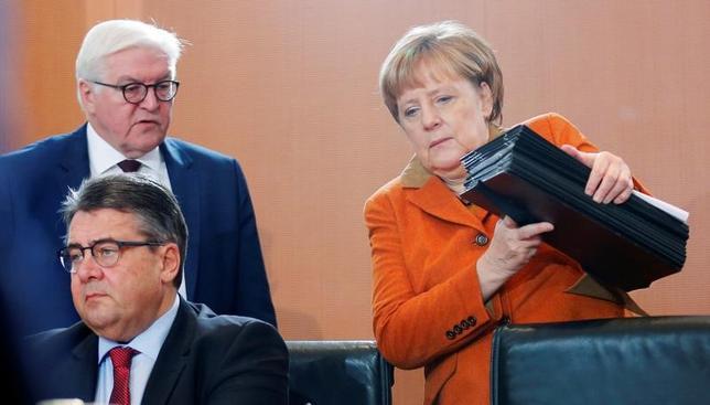 2月3日、ドイツ政府の報道官は、ギリシャ経済の安定化が必要だという認識で政府内の見解は一致していると語った。写真はガブリエル独外相(写真左前)とメルケル首相(右)ベルリンで昨年12月撮影(2017年 ロイター/Hannibal Hanschke)
