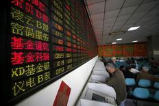 Инвесторы в брокерском доме в Шанхае. Китайские фондовые индексы выросли в понедельник, однако активность торгов была низкой, поскольку инвесторы проявляли осторожность, опасаясь ужесточения политики центробанка после того, как Пекин неожиданно повысил краткосрочные процентные ставки на прошлой неделе.  REUTERS/Aly Song/File Photo
