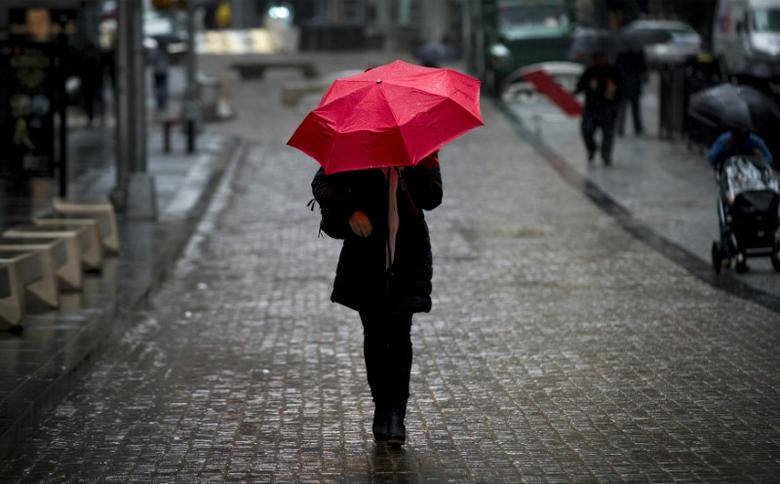 A woman walks on Broad St. past the New York Stock Exchange during the morning commute April 30, 2014. REUTERS/Brendan McDermid