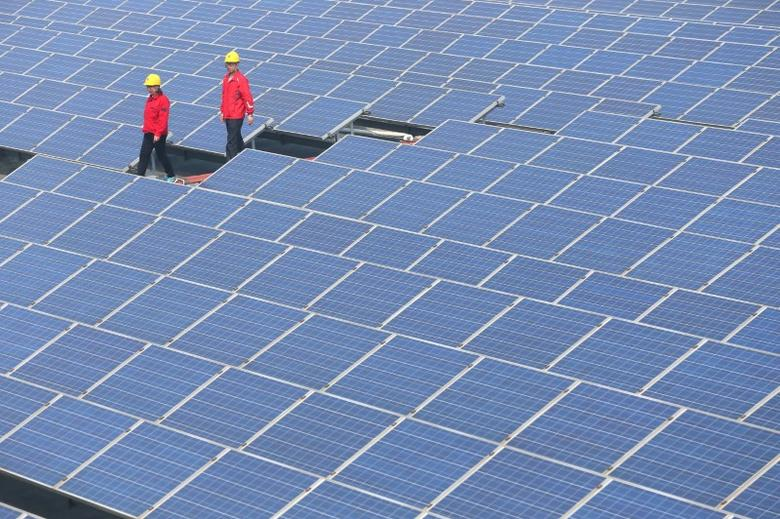 Workers walk past solar panels in Jimo, Shandong Province, China, April 21, 2016. China Daily/via REUTERS