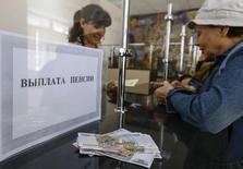Женщина получает пенсию в почтовом отделении в Симферополе. 25 марта 2014 года. Российские власти отложили на 2019 год внедрение пенсионной реформы, в ходе которой обязательный накопительный элемент будет отменен и гражданам предложат формировать накопления добровольно. REUTERS/Shamil Zhumatov