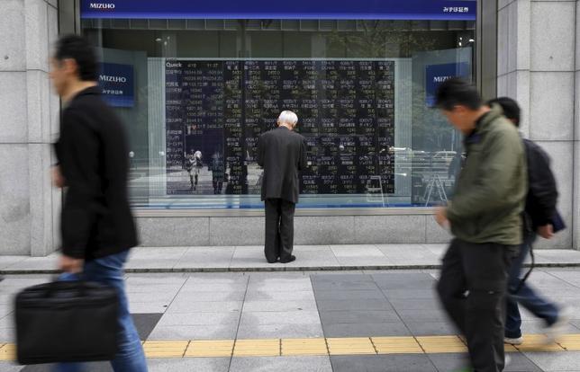 2月14日、寄り付きの東京株式市場で、日経平均株価は前営業日比19円71銭高の1万9478円86銭となり、小幅続伸して始まった。写真は株価ボードを眺める男性、都内で昨年4月撮影(2017年 ロイター/Toru Hanai)