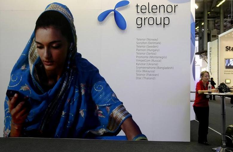 A visitor rests under a Telenor Group sign at the GSMA Mobile World Conference in Barcelona, Spain, February 18, 2009.    REUTERS/Gustau Nacarino/File Photo
