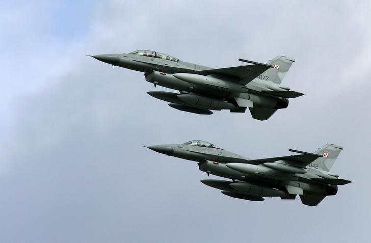 FILE PHOTO -  Two of the first four Polish Air Force F-16 fighter jets arrive at the Krzesiny airport in western Poland, near the city of Poznan November 9, 2006.   REUTERS/Peter Andrews/File Photo