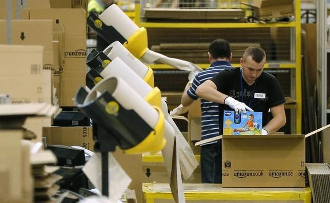 A worker packs completed orders into boxes at the Amazon fulfilment centre in Peterborough, central England November 28, 2013. REUTERS/Phil Noble/File Photo