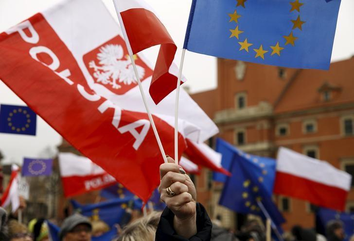People hold EU and Polish flags as they gather during a pro-democracy demonstration at the Old Town in Warsaw, Poland January 9, 2016. REUTERS/Kacper Pempel/Files