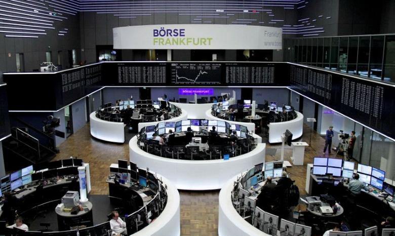 Traders work at their desks in front of the German share price index, DAX board, at the stock exchange in Frankfurt, Germany, January 17, 2017. REUTERS/Staff/Remote/Files