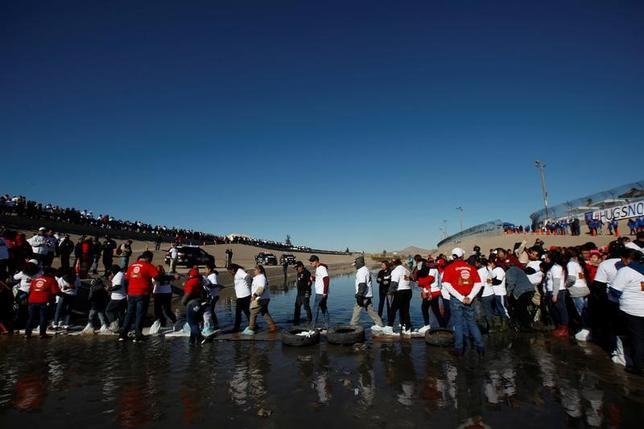 2月23日、米国が打ち出した不法移民に関する新たな指針をめぐり、メキシコ当局者から批判の声が相次いだ。写真は、米・メキシコの国境になっているリオ・ブラボー川で、離れて暮らす家族の再会イベント「Hugs Not Walls」に集まる移民。1月撮影(2017年 ロイター/Jose Luis Gonzalez)