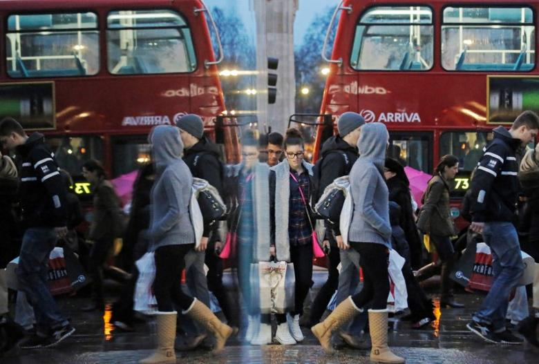 Shoppers are reflected in a shop window as they walk along Oxford Street on the last Saturday before Christmas, in London  December 21, 2013.   REUTERS/Luke MacGregor/File Photo