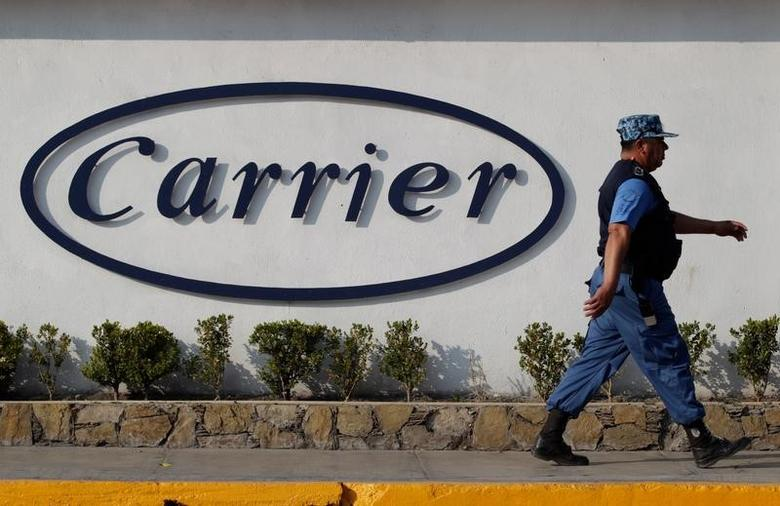 A private security guard walks past a logo of Carrier Corp outside the air conditioner plant, a unit of United Technologies Corp, in Santa Catarina, on the outskirts of Monterrey, Mexico, February 17, 2016. REUTERS/Daniel Becerril