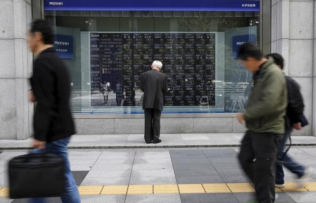 2月24日、寄り付きの東京株式市場で、日経平均株価は前営業日比139円35銭安の1万9232円11銭となり、続落して始まった。写真は株価ボードを眺める男性、都内で昨年4月撮影(2017年 ロイター/Toru Hanai)
