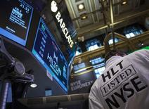 A trader wears a Hilton robe during the company's IPO on the floor of the New York Stock Exchange (NYSE), December 12, 2013. REUTERS/Brendan McDermid