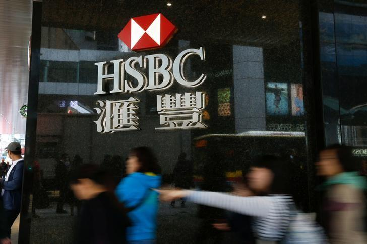 People walk past a major branch of HSBC at the financial Central district in Hong Kong, China February 21, 2017.      REUTERS/Bobby Yip
