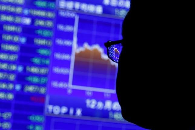 3月2日、米資産運用会社、アライアンス・バーンスタインの日本バリュー株式共同最高投資責任者の堀川篤氏は、日本株はグローバルでみて割安であると指摘。写真は都内の株価ボードを眺める男性。2015年8月撮影(2017年 ロイター/Thomas Peter)