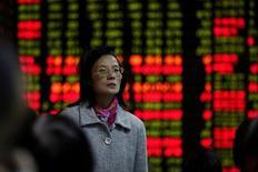 Una inversora observa una pantalla electrónica que muestra información de acciones en una casa de valores en Shanghái, China, 9 de noviembre del 2016.Las acciones chinas cayeron el jueves en medio de una retirada de los compradores por la especulación de una posible subida de las tasas de interés en Estados Unidos a finales de este mes.REUTERS/Aly Song