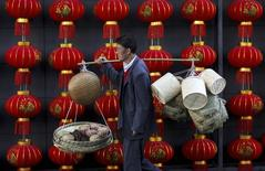A basket vendor walks past red lanterns serving as decorations to celebrate the new year outside a shopping mall in Kunming, Yunnan province January 6, 2015. REUTERS/Stringer