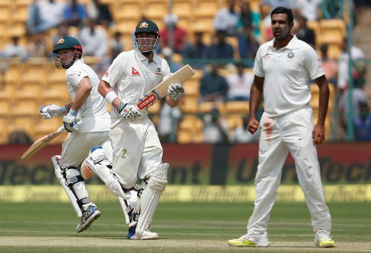 Cricket - India v Australia - Second Test cricket match - M Chinnaswamy Stadium, Bengaluru, India - 05/03/17. Australia's Matt Renshaw and Shaun Marsh run between the wickets as India's Ravichandran Ashwin (R) looks on. REUTERS/Danish Siddiqui