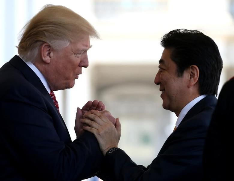 Japanese Prime Minister Shinzo Abe is greeted by U.S. President Donald Trump (L) ahead of their joint news conference at the White House in Washington, U.S., February 10, 2017.  REUTERS/Joshua Roberts