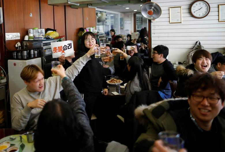 People make a toast as they celebrate after hearing that President Park Geun-hye's impeachment was accepted, at a restaurant near the Presidential Blue House in Seoul, South Korea, March 10, 2017. The sign reads ''We won''.  REUTERS/Kim Hong-Ji