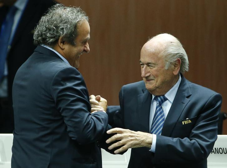 UEFA President Michel Platini (L) congratulates FIFA President Sepp Blatter after he was re-elected at the 65th FIFA Congress in Zurich, Switzerland, May 29, 2015. REUTERS/Ruben Sprich/Files
