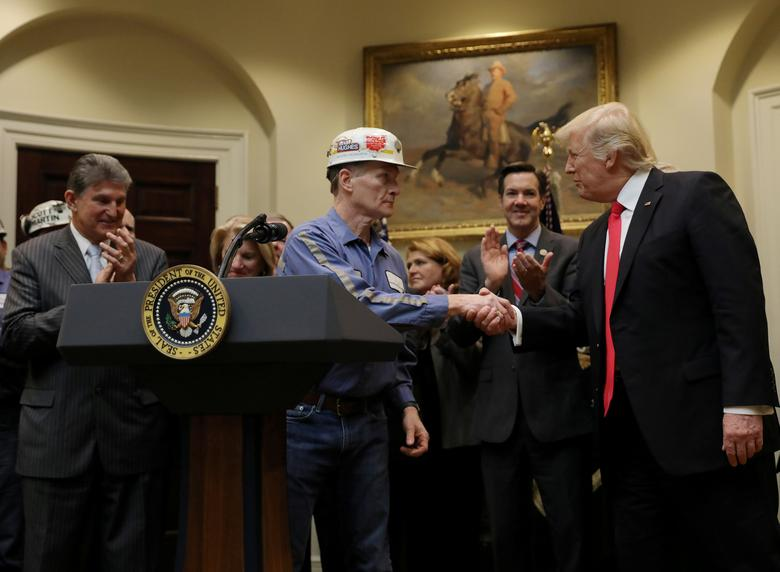 FILE PHOTO - A coal miner worker shakes hands with U.S. President Donald Trump speaks as he prepares to sign Resolution 38, which nullfies the ''stream protection rule'' addressing the impacts of surface coal mining operations on surface water, groundwater, and the productivity of mining operations sites, at the White House in Washington, U.S. on February 16, 2017. REUTERS/Carlos Barria/File Photo