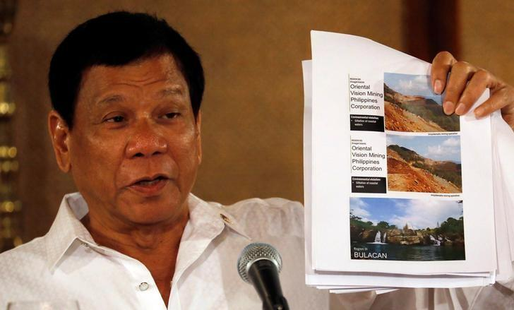 Philippine President Rodrigo Duterte shows pictures of mines during a news conference in Manila, Philippines March 13, 2017. REUTERS/Erik De Castro/Files