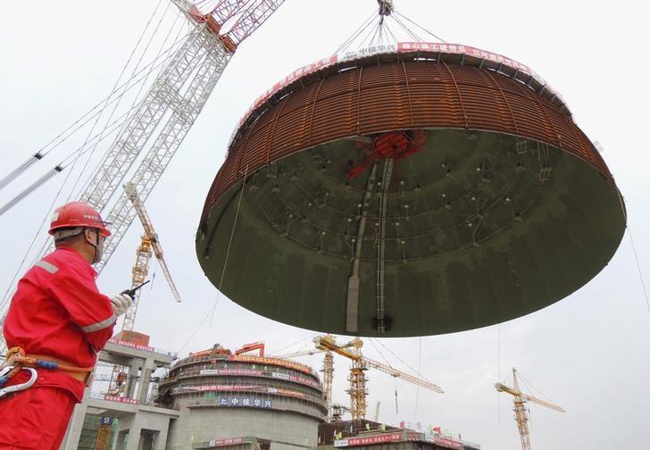A worker looks on as the dome roof of a generator unit is lifted to be installed, at Tianwan Nuclear Power Plant, in Lianyungang, Jiangsu province, China, September 26, 2015. REUTERS/Stringer/Files