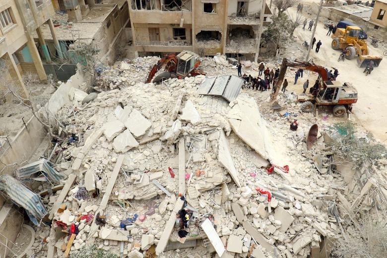 Civil Defence members and civilians remove rubble in a damaged site after an airstrike on Idlib city, Syria March 15, 2017. REUTERS/Ammar Abdullah